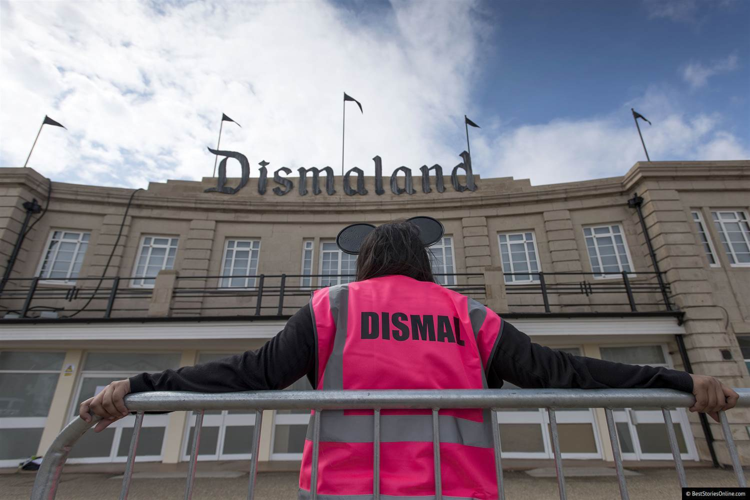 Pictured: A 'Dismaland' employee slacks off outside the exhibition's entrance.